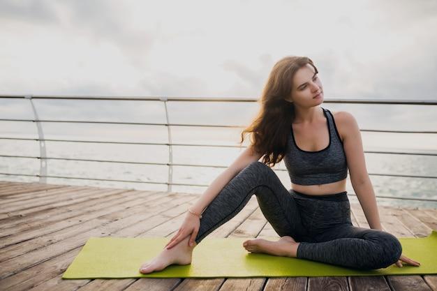 Het jonge slanke mooie aantrekkelijke vrouw ontspannen op yogamat in de ochtend op zonsopgang door overzees, gezonde levensstijl, fitness sport Gratis Foto
