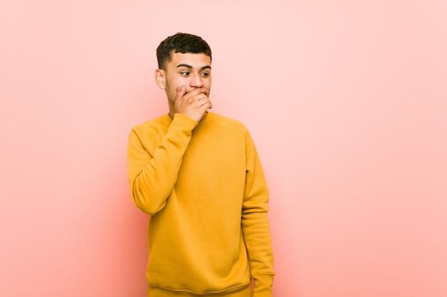 Het jonge spaanse mens nadenkende kijken aan een exemplaarruimte die mond behandelen met hand. Premium Foto
