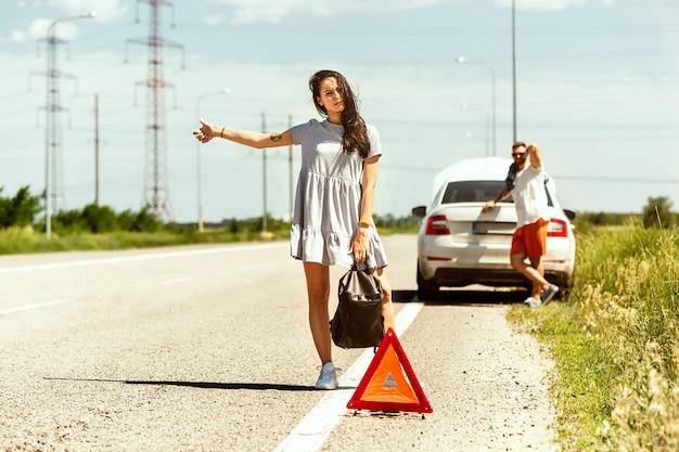 Het jonge stel heeft de auto kapotgemaakt terwijl ze onderweg waren om uit te rusten. ze proberen andere chauffeurs tegen te houden en om hulp te vragen of te liften. relatie, problemen onderweg, vakantie. Gratis Foto