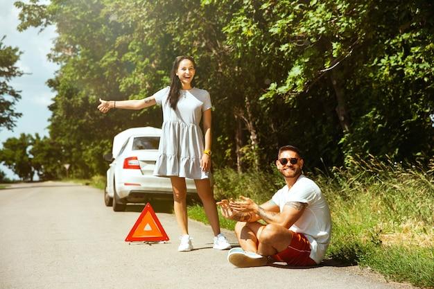 Het jonge stel heeft de auto kapotgemaakt terwijl ze onderweg waren om uit te rusten Gratis Foto
