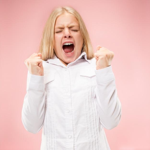 Het jonge toevallige tienermeisje schreeuwen. roepen. huilende emotionele tiener die op roze ruimte gilt. vrouwelijke halve lengte portret Gratis Foto