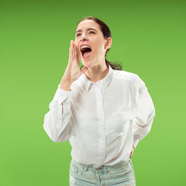 Het jonge toevallige vrouw schreeuwen. roepen. huilende emotionele vrouw die op groene studioachtergrond gilt. vrouwelijke halve lengte portret. Gratis Foto