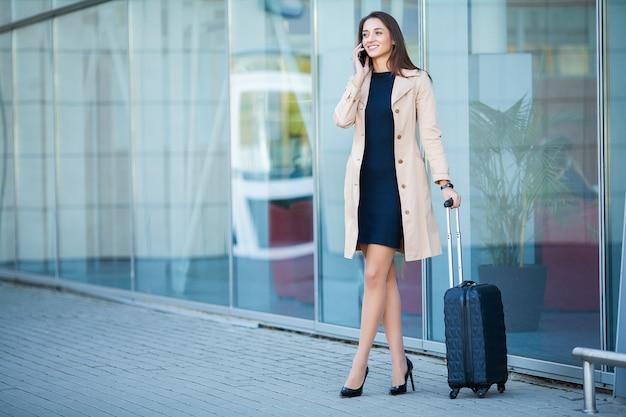 Het jonge toevallige wijfje gaat bij luchthaven bij venster met koffer wachtend op vliegtuig Premium Foto