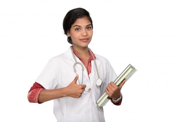 Het jonge vrouw boek van de artsenholding met stethoscoop Premium Foto