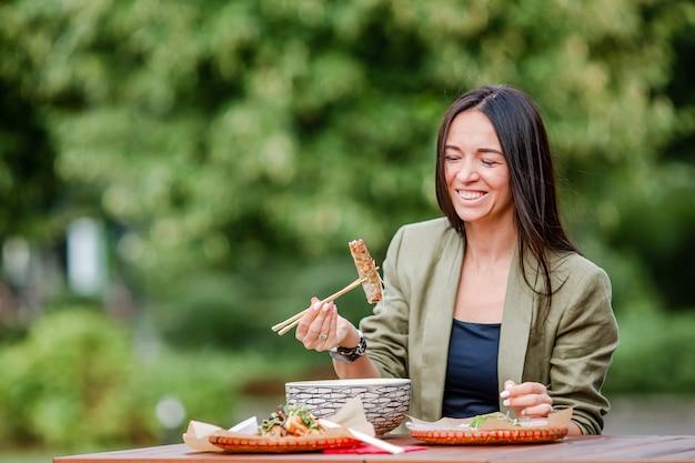 Het jonge vrouw eten haalt noedels op de straat weg Premium Foto