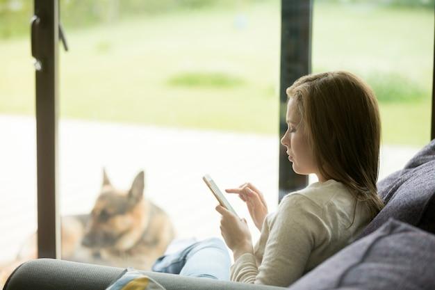 Het jonge vrouw ontspannen op bank die smartphone apps binnen huis gebruiken Gratis Foto