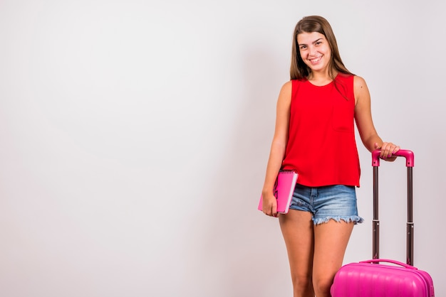 Het jonge vrouw stellen met roze koffer en notitieboekje op witte achtergrond Gratis Foto