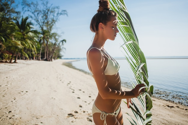 Het jonge vrouw stellen op zandstrand onder palmblad Gratis Foto
