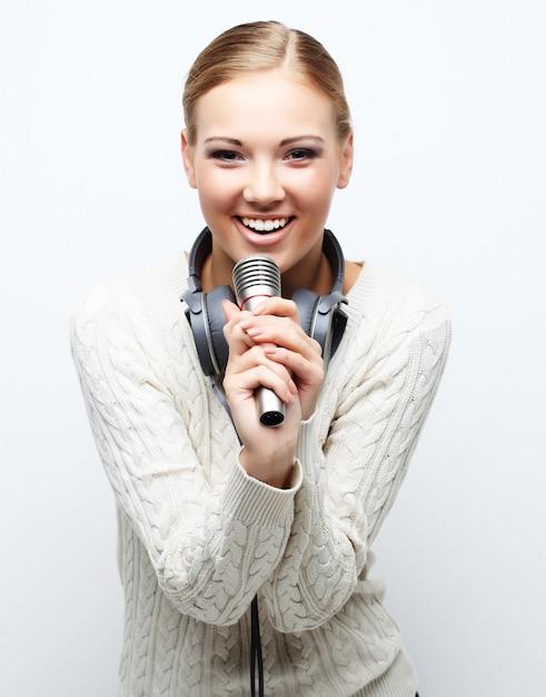 Het jonge vrouw zingen in microfoon met hoofdtelefoons in studio op wit Premium Foto
