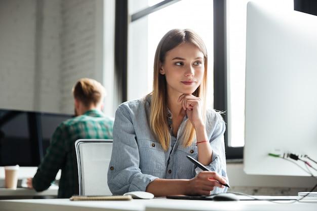 Het jonge vrouwenwerk in bureau die computer en grafische tablet gebruiken Gratis Foto