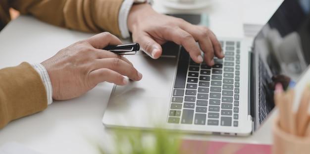 Het jonge zakenman typen op laptop computer terwijl het werken aan zijn huidig project Premium Foto