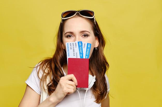 Het kaukasische meisje behandelt de helft van haar gezicht met vliegtickets en paspoort op een gele achtergrond. Premium Foto