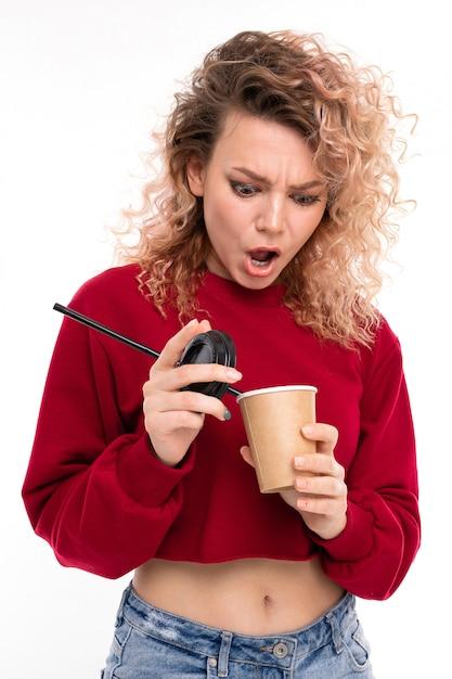 Het kaukasische meisje met krullend eerlijk haar drinkt koffie en is verrast, geïsoleerd portret Premium Foto