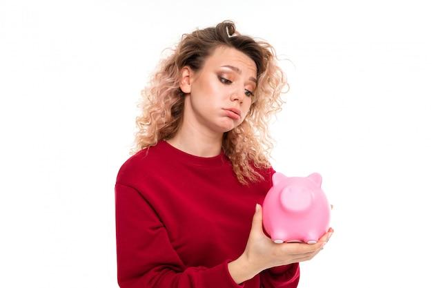 Het kaukasische meisje met krullend eerlijk haar houdt een roze die varken moneybox, portret op wit wordt geïsoleerd Premium Foto