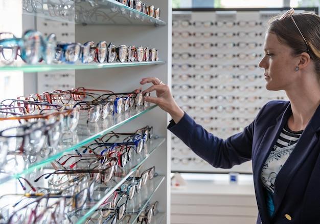 Het kiezen van een bril in de optiekwinkel door een jonge vrouw Premium Foto