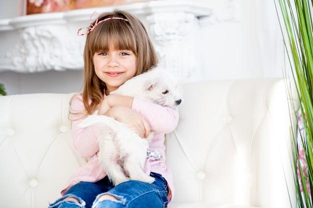 Het kind koestert een wit terriërpuppy Premium Foto