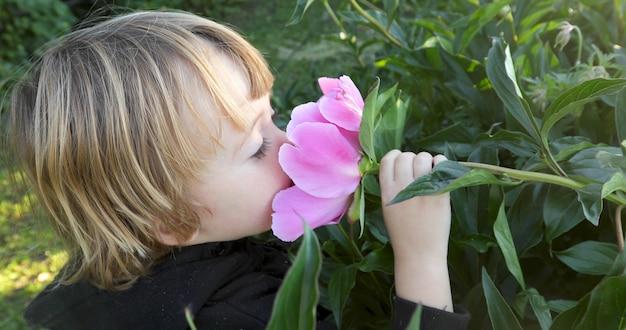 Het kind snuift een bloem Premium Foto