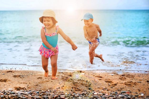 Het kind speelt en spettert in de zee Premium Foto