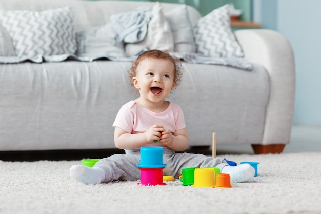 Het kind speelt op de vloer op een licht tapijt met licht speelgoed, bouwt een toren Premium Foto