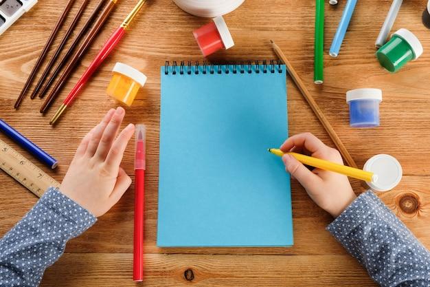 Het kind tekent een notitieboekje met viltstiften en verf. Premium Foto