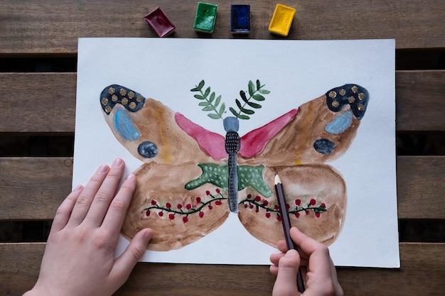 Het kind tekent een ongewoon mooie vlinder met aquarellen en potloden Premium Foto