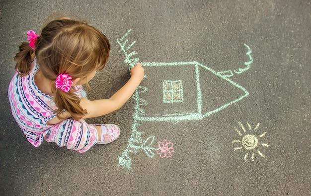 Het kind trekt het huis met krijt op het asfalt. selectieve aandacht. Premium Foto