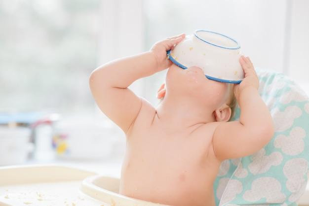 Het kind zette een kom op zijn hoofd Premium Foto