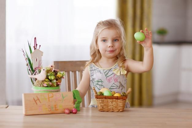 Het kind zit aan de vakantietafel met een mand met paaseieren. houdt een ei in zijn hand en denkt na Premium Foto