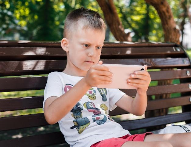 Het kind zit in het park op een bank met een gadget. kinderen gebruiken gadgets. een jongen speelt een spel op een mobiele telefoon. Premium Foto