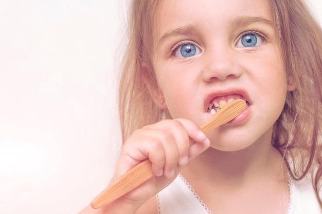 Het kindmeisje 3 jaar oud borstelt haar tanden met een bamboetandenborstel. een mooi kind met grote blauwe ogen redt de planeet van plastic. Premium Foto