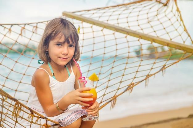Het kindmeisje drinkt cocktail op het strand. Premium Foto