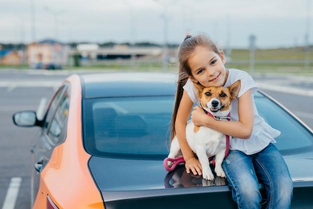 Het kleine aantrekkelijke vrouwelijke kind omhelst haar favoriete hond, zit samen bij boomstam van auto Premium Foto