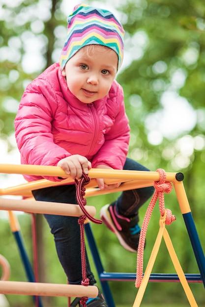Het kleine babymeisje dat bij openluchtspeelplaats speelt Gratis Foto