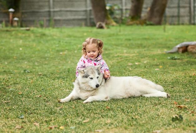 Het kleine babymeisje die met hond tegen groen gras in park spelen Gratis Foto