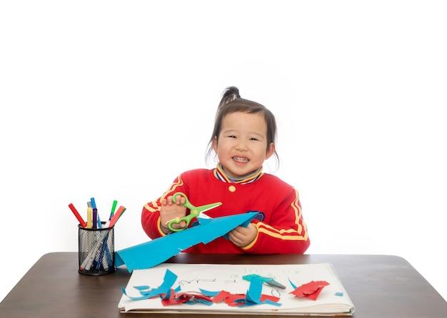 Het kleine meisje speelt met het snijden van papier Premium Foto