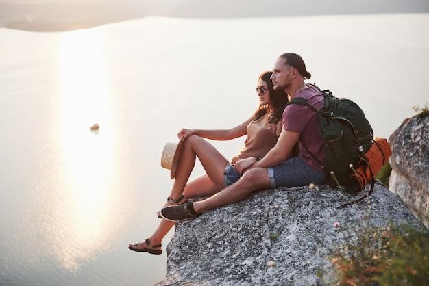 Het koesteren van paar met rugzakzitting bovenop rotsberg die van meningskust een rivier of een meer geniet. Gratis Foto
