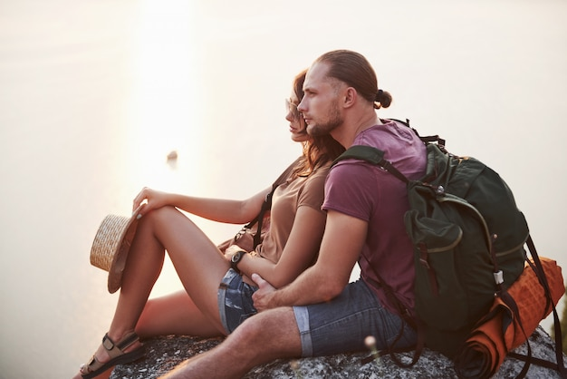 Het koesteren van paar met rugzakzitting dichtbij de brand bovenop berg Gratis Foto