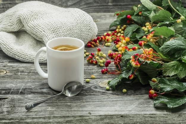 Het kopje thee op een mooie houten achtergrond met winter trui, bessen, herfst Gratis Foto
