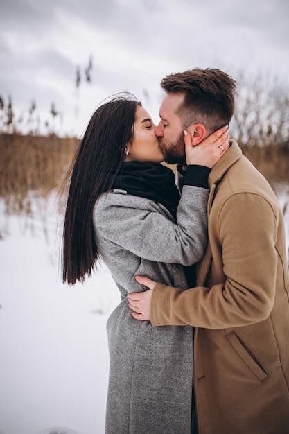 Het kussen van ccouple in de winterpark Gratis Foto