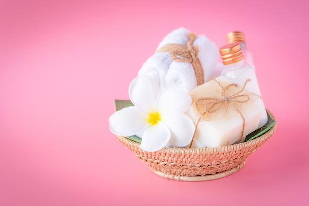 Het kuuroordconcept, nam vloeibare fles, melkzeep, witte handdoeken in houten dienblad op roze toe Premium Foto