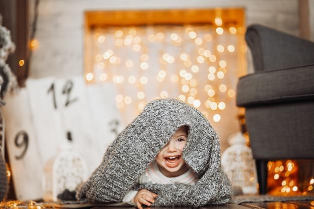 Het lachende meisje verbergt onder grijze deken op de vloer Premium Foto