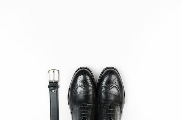 Het lederen schoenen en riem van mannen op een witte achtergrond Premium Foto