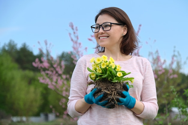 Het lenteportret van het wijfje van middelbare leeftijd in handschoenen met gele primrosebloemen dient binnen tuin in Premium Foto