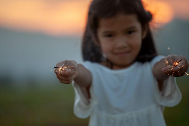 Het leuke aziatische kindmeisje speelt met vuursterretjes op het festival in het padieveld Premium Foto