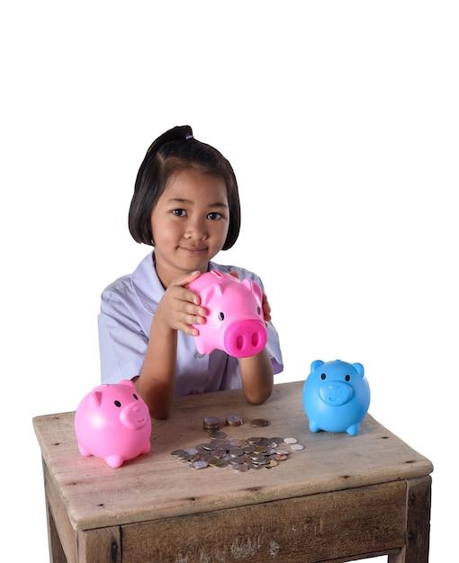 Het leuke aziatische meisje heeft pret met veel die spaarvarken op witte achtergrond wordt geïsoleerd Premium Foto