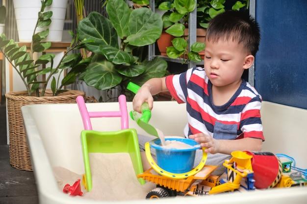 Het leuke aziatische peuterjongen spelen met alleen zand thuis, kind het spelen met stuk speelgoed bouwmachines, creatief spel voor jonge geitjesconcept Premium Foto