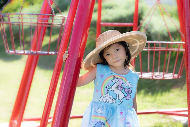 Het leuke meisje draagt een grote hoed en speelt in openluchtpark Premium Foto