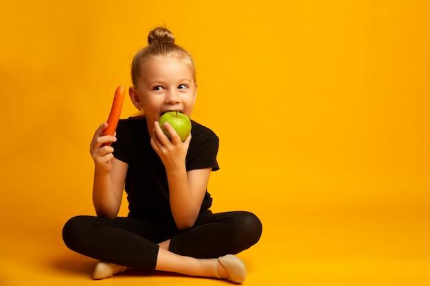 Het leuke meisje eet wortel en appelen, die over geel worden geïsoleerd. gezond eten Premium Foto