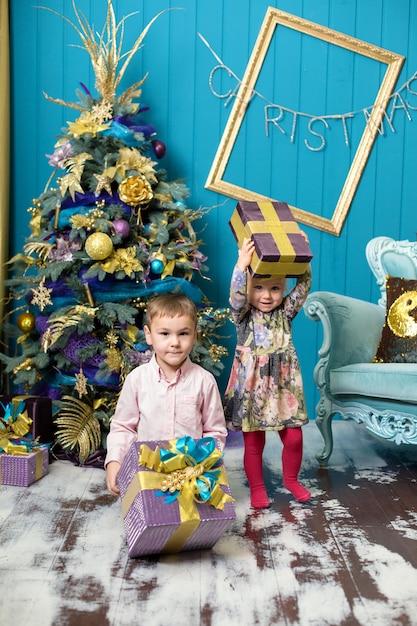 Het leuke meisje en de jongen glimlachen en houden giften onder de kerstboom. Premium Foto