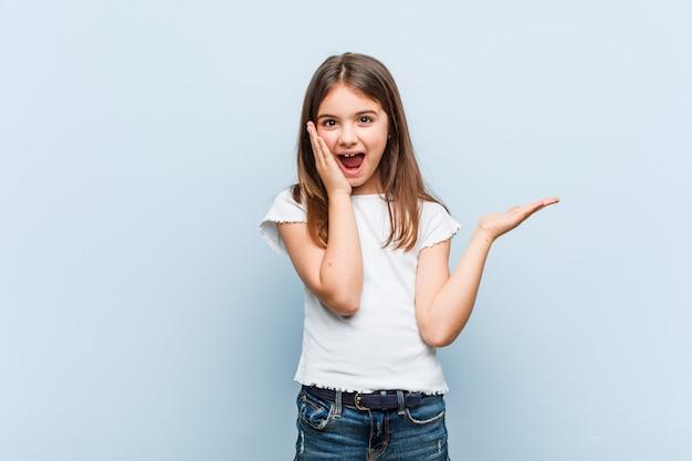 Het leuke meisje houdt exemplaarruimte op een palm, houdt wang overhandig verbaasd en opgetogen Premium Foto